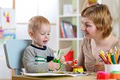 Woman teaches child handcraft. Mother looks at her little son how he cuts color paper poster