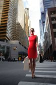 attractive girl in red dress with shopping bags crossing a city street poster