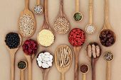 Dried super health food selection in wooden spoons over natural paper background. High in antioxidants, minerals, vitamins and dietary fiber. poster