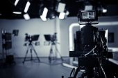 TV Studio live broadcasting.Recording show.TV NEWS program studio with video camera lens and lights.Positioned stage big professional broadcasting camera with headphones poster