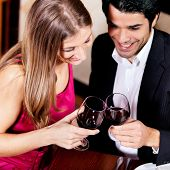 Young couple - man and woman - in a restaurant drinking glasses of red wine poster