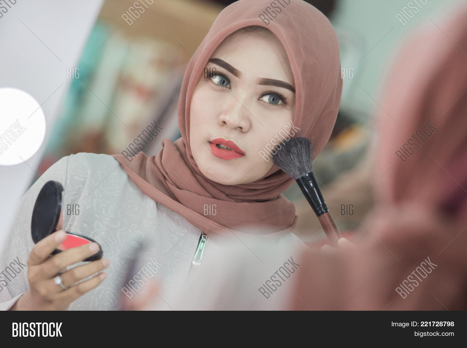 Beauty muslim woman with hijab applying makeup. Beautiful girl looking in  the mirror and applying