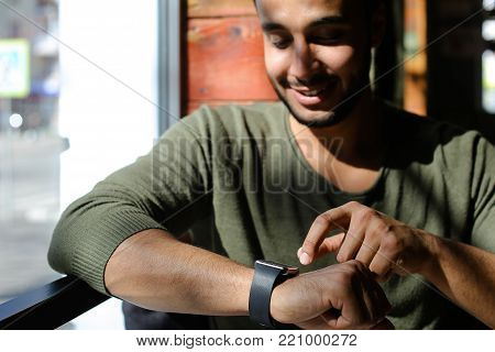 Arabian sits near window and uses smart watch in caf . Person dressed in khaki pullover and white jeans. Boy has dimples, beard, full lips and black hair. Concept of modern technologies and good atmosphere, places for resting.
