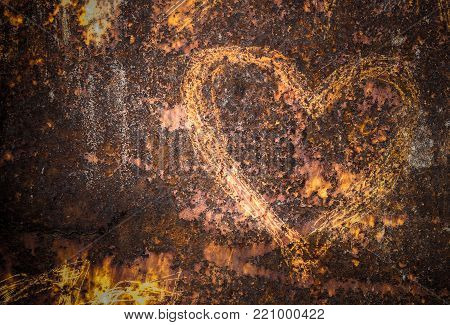 Heart carved on an old and rusty wall