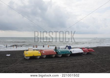 photo pedal boat catamarans of different flowers on the bank sea. Travel or sea vacations concept