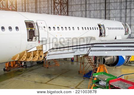 Passenger aircraft on maintenance, a view of the rear of the fuselage in airport hangar