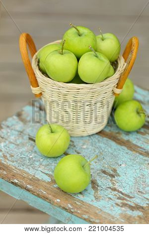 Green apples in a wicker basket on a wooden light background. Selectuve focus.
