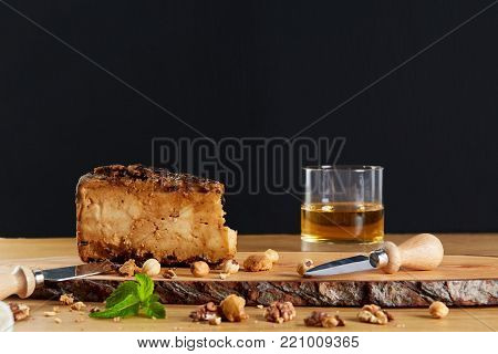 A bar of cheese with a glass of whiskey. Cheese tasting. Elite cheese with nuts on a wooden board