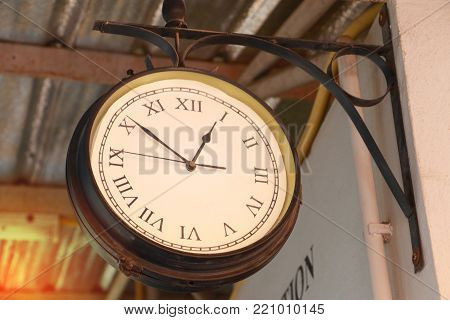Close up of vintage death clock hang on the vintage zinc roof at vintage train station in province of asia. Clock in train station with copy space for text. poster