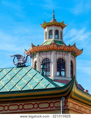 Close-up architectural detail of the historical pavilion in Chinese style with a dragon, a turret, a pointed roof, with a spire, oval windows, a pattern in the Alexander Park in Pushkin in St. Petersburg in early May on a warm sunny day in late spring