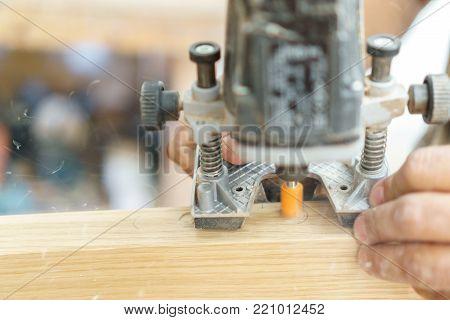 Carpenter working over door edge creating hinges holes, blurred motion