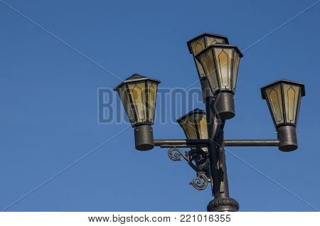Old black lantern on the background with blue sky