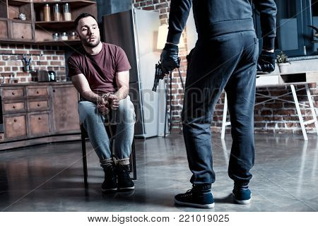 Killer. Shocked alarmed bearded man sitting with his hands tied while a burglar standing near him and holding a gun