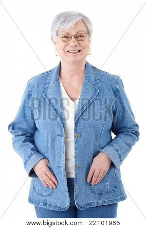Happy senior woman standing over white background, wearing denim jacket, smiling.?