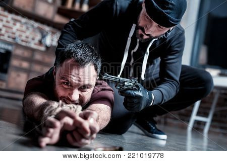 Trying to escape. Panic shocked bearded man lying on the floor with his hands tied and trying to escape while a killer sitting near him and holding a gun at his head