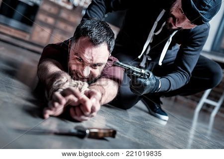 Last hope. Panic intimidated bearded man lying on the floor with his hands tied and trying to escape while a killer sitting near him and holding a gun at his head