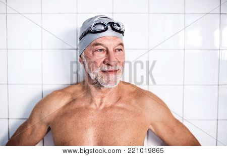 Portrait of a senior man standing against white background in an indoor swimming pool.. Active pensioner enjoying sport.