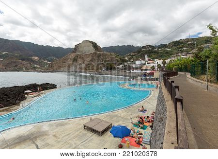 PORTO DA CRUZ, MADEIRA, PORTUGAL - SEPTEMBER 11, 2016: People rest by the Swimming Pool in Porto da Cruz on Medeira. Portugal