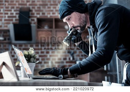Hacker. Serious experienced bearded hacker standing and holding a torch and looking for something on the laptop