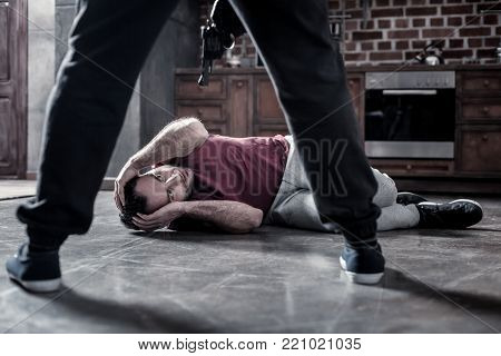 Victim. Frightened dark-eyed bearded man lying on the floor and covering his head with hands and a killer holding a pistol at his head