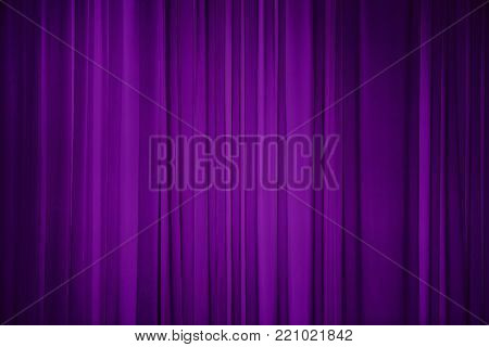 Purple fabric background. Draped curtain hanging close-up. Decorative Wallpaper or Web Banner With Copy Space for design.