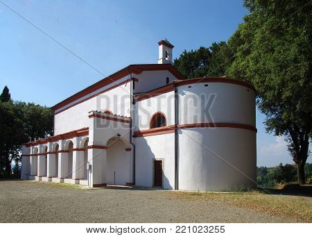 isolated white church with curved apse and red finishes in the green vegetation with side arches