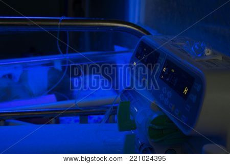 Newborn Baby Under Blue Uv Light For Phototheraphy On Infant Warmer In Neonatal Intensive Care Unit.