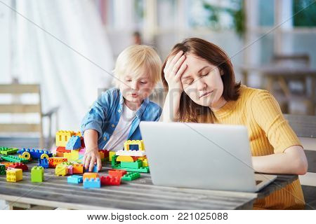 Adorable little boy playing with colorful plastic construction blocks while his mother working on her laptop. Childcare and work concept