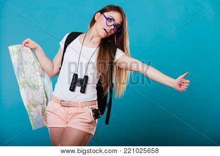 Travel vacation hitchhiking concept. Summer girl with map thumbing and hitch hiking on blue