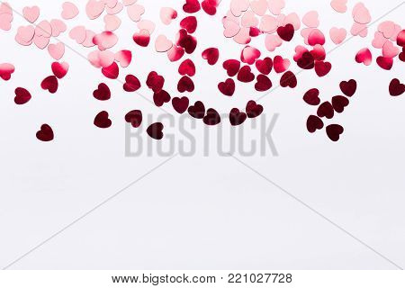 Small light to dark red paper hearts on white background with copy space. Lover's holiday confession or proposal concept