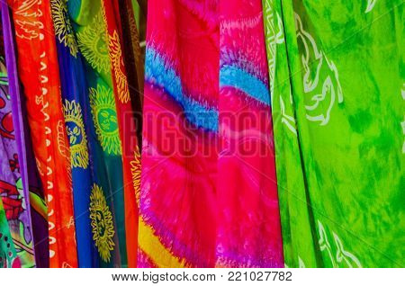 A row of colourful sarong scarves pegged outside a shop on a beach in Tobago.