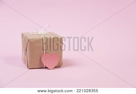 gift box and red heart for valentines day on pink background.