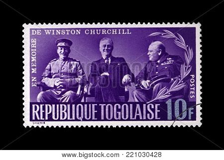 TOGO - CIRCA 1965: cancelled stamp printed in Togo shows Stalin, Roosevelt and Churchill at Yalta conference during World War II, circa 1965. Vintage post stamp isolated on black background.