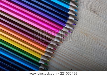 Bright colorful pencils on wooden table. Multicolored crayons background. School, drawing an sketching supplies.