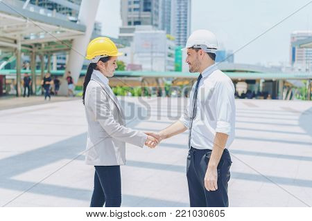Two engineer handshaking after success project at site. Couple wearing safety helmet and handshake with city background. Concept of business partnership meeting.