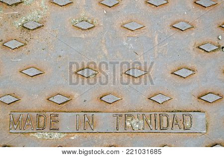 A cast iron drain cover with Made in Trinidad embossed on it.  Scarborough, Tobago.
