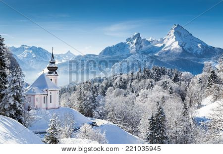 Panoramic view of beautiful winter wonderland mountain scenery in the Bavarian Alps with pilgrimage church of Maria Gern and famous Watzmann massif in the background, Nationalpark Berchtesgadener Land, Bavaria, Germany