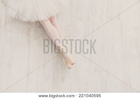 Young ballerina legs in pointe shoes at white wooden floor background, top view with copy space. Ballet practice, slim graceful feet of ballet dancer.