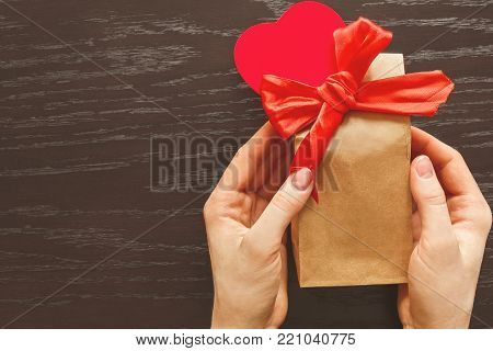 Giving a gift, Packed in crafty package in celebration of Valentine's day. Attached bow and red heart, plush