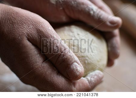 Old man holding a dough. Cook preparing raw dough for pizza. Handmade.