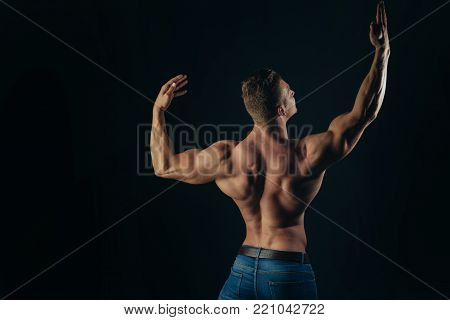 Healthy lifestyle, bodycare concept. Athlete man with bare torso in blue jeans, back view. Sportsman show muscles on dark background. Sport, bodybuilding, fitness, copy space poster
