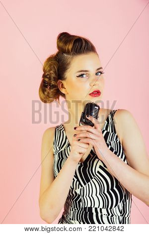 Beauty and vintage fashion. Pin up young girl on pink background, radio. Woman singer with stylish retro hair and makeup. Music, look and retro style, pinup. Girl in glasses sing in microphone.