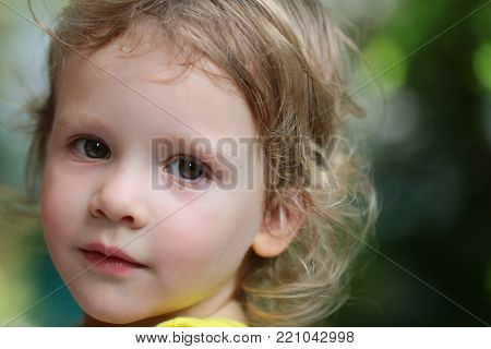 Baby girl with green eyes on cute face and blond hair on natural environment. Child, childhood, family. Innocence, infancy, future concept