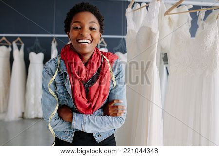 Female bridal store owner looking at wedding gown with a diary in hand. Dressmaker with diary examining bridal wear pattern. poster