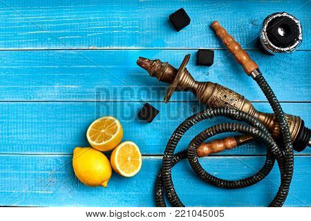 Tobacco background. Turkish smoking hookah with tobacco flavor of ripe lemon. Top view of a blue wooden background. Still life. Copy space. Flat lay