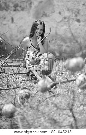 Girl smile at dry tree branches on natural landscape. Beauty, look, hairstyle. Teenager with long hair in summer dress. Teen, teenage, youth, lifestyle. Fashion, style concept, black and white