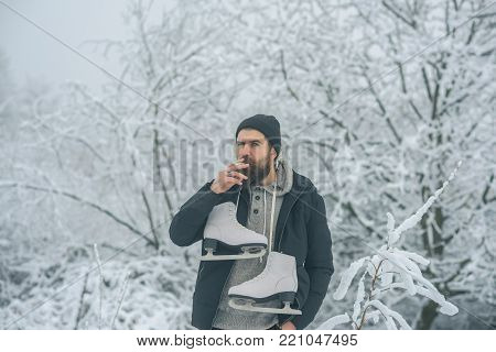 Bearded man smoking cigarette with skates in snowy forest. Man in thermal jacket, beard warm in winter. skincare and beard care in winter. Winter sport, Christmas. Temperature, freezing, cold snap.