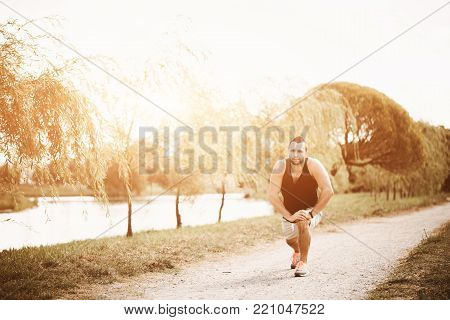 Running in the evening sunlight. Active sport concept. Healthy sportsman does exercises on the street. Runner in park. Tired athlete in sportswear get a pause.