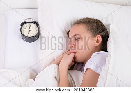 girl sleeps and sucks her thumb, a habit since childhood