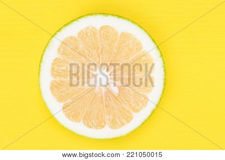 Sweetie fruit is cut into a round half, on a yellow background